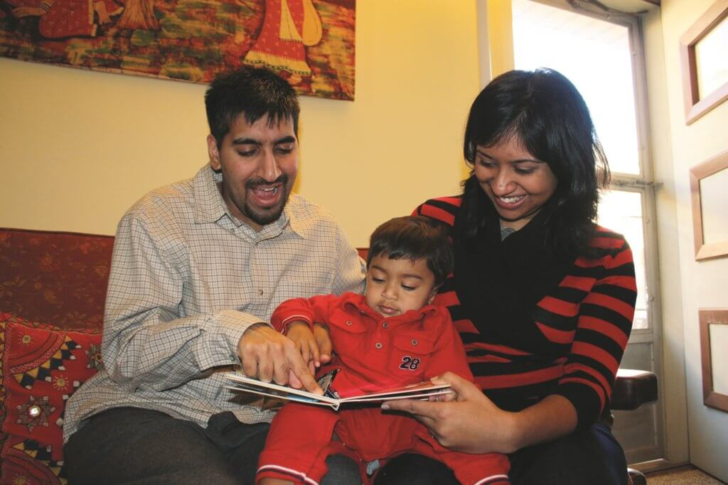 Parents reading a book to toddler