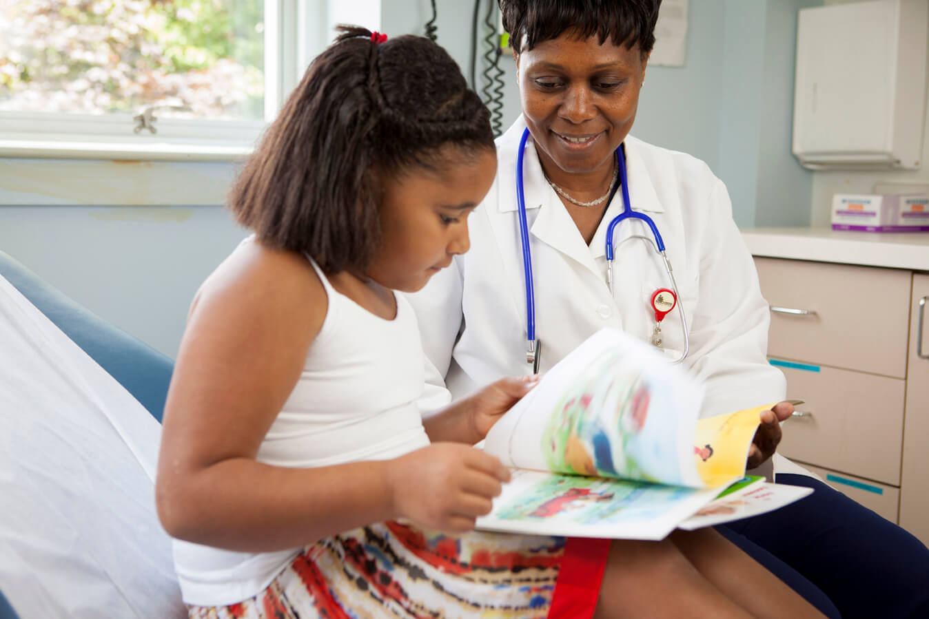 Young girl reading with doctor