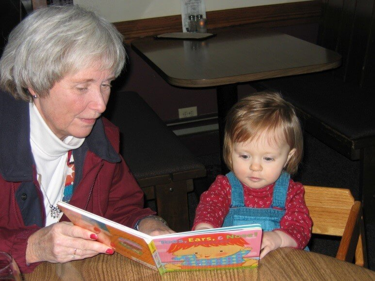 Grandmother and small child reading together