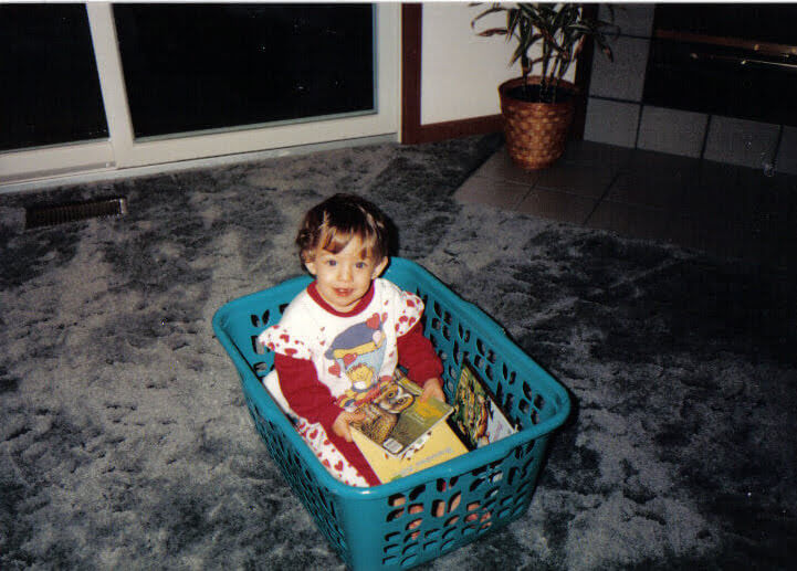 young girl reading in laundry basket