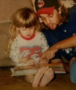 young girl and parent reading aloud