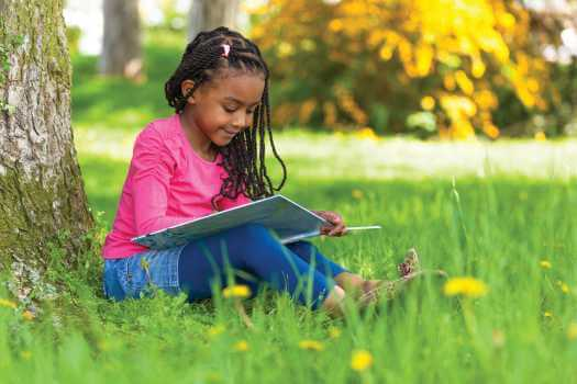 Outdoor portrait of young girl reading under tree, events