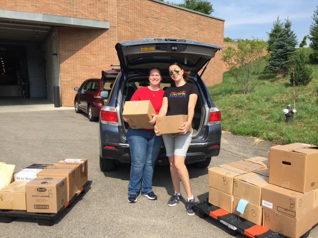 Two Epic employees with their donation of books to Reach Out and Read Wisconsin