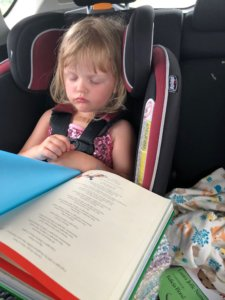 young girl reading and sleeping in the car