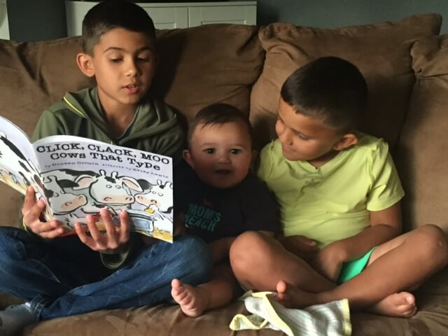 young boys read books aloud together